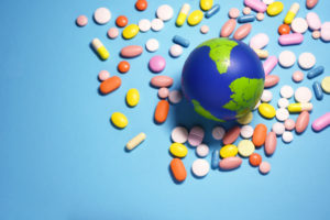 pills surrounding globe of the earth on a blue background; healthy planet concept; Earth Day